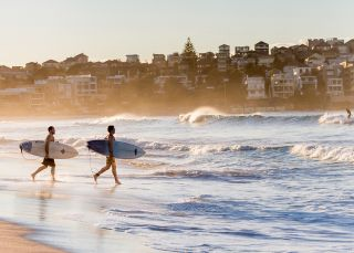 Surfers heading for a morning surf at Bondi Beach