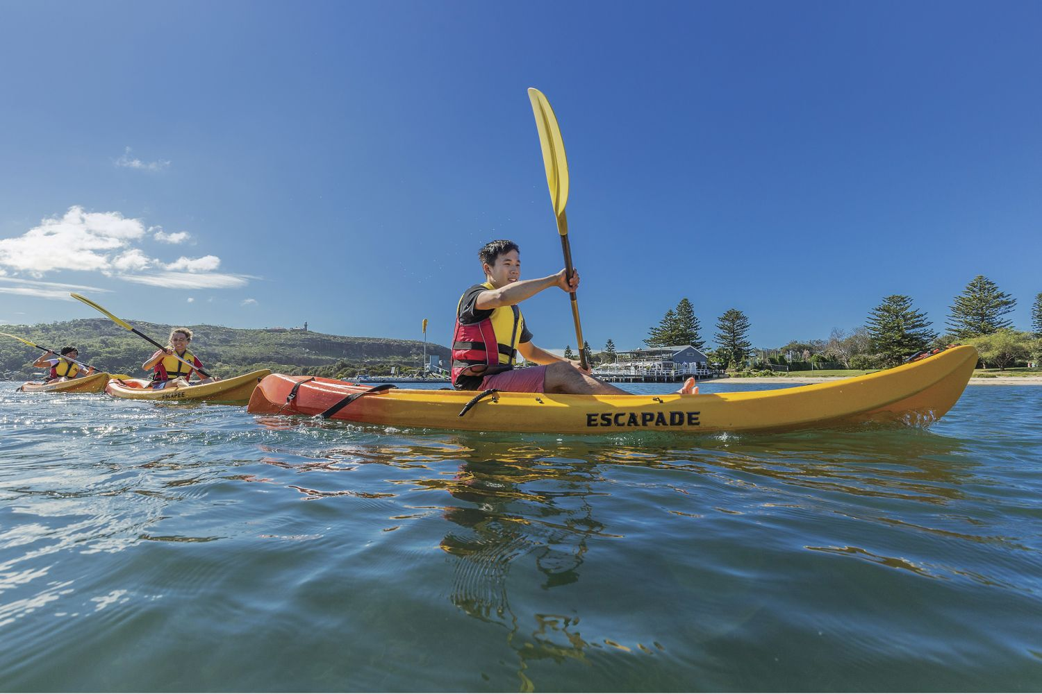Friends kayaking on shimmering Pittwater near the Boathouse Restaurant, Palm Beach