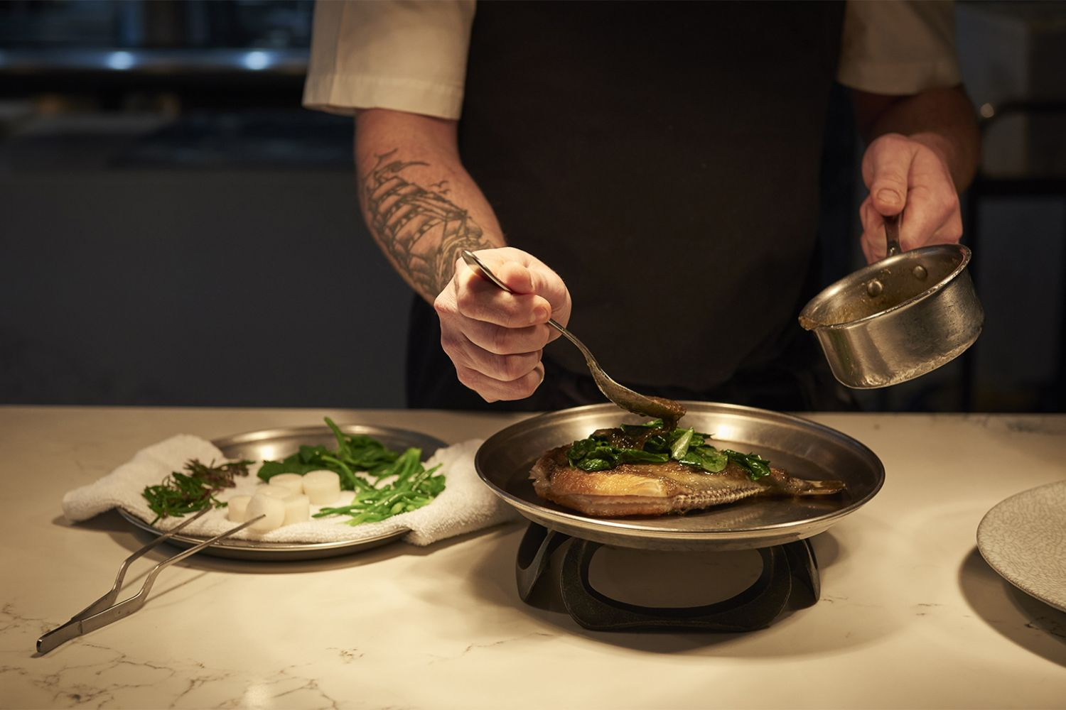 Chef de Cuisine, Rob Cockerill placing the finishing touches on a dish at Bennelong Restaurant, Sydney