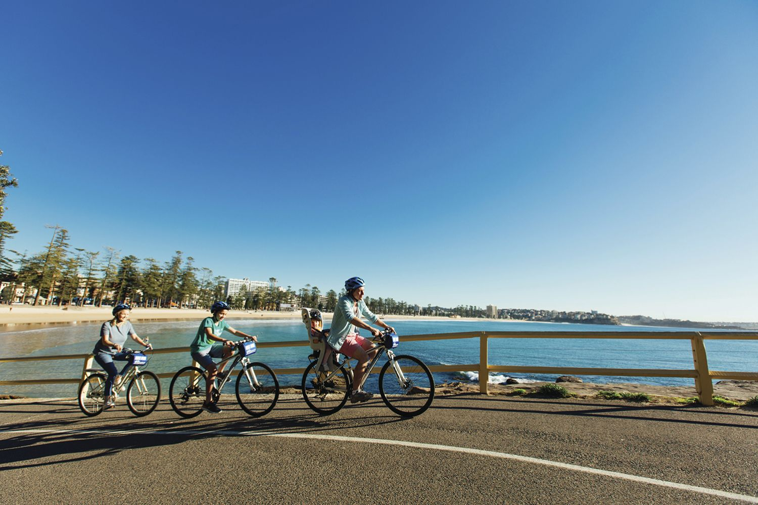 Family enjoying a bike ride at Manly Beach on Sydney's northern suburbs