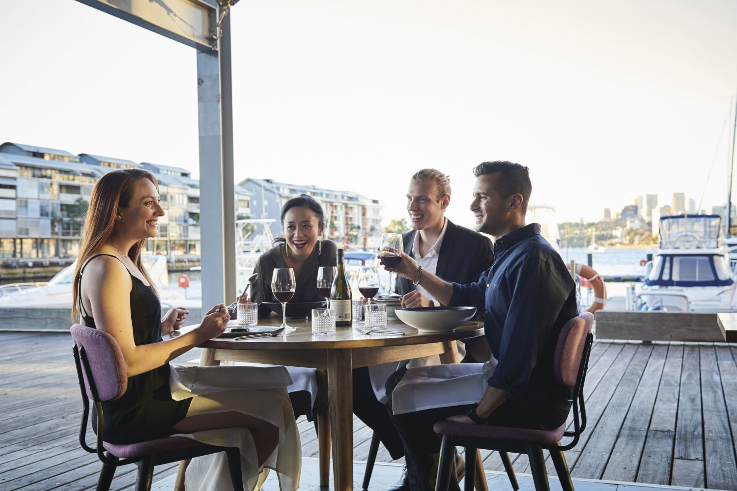 Friends enjoying food and drink at waterside restaurant LuMi Bar & Dining in Pyrmont, Sydney City