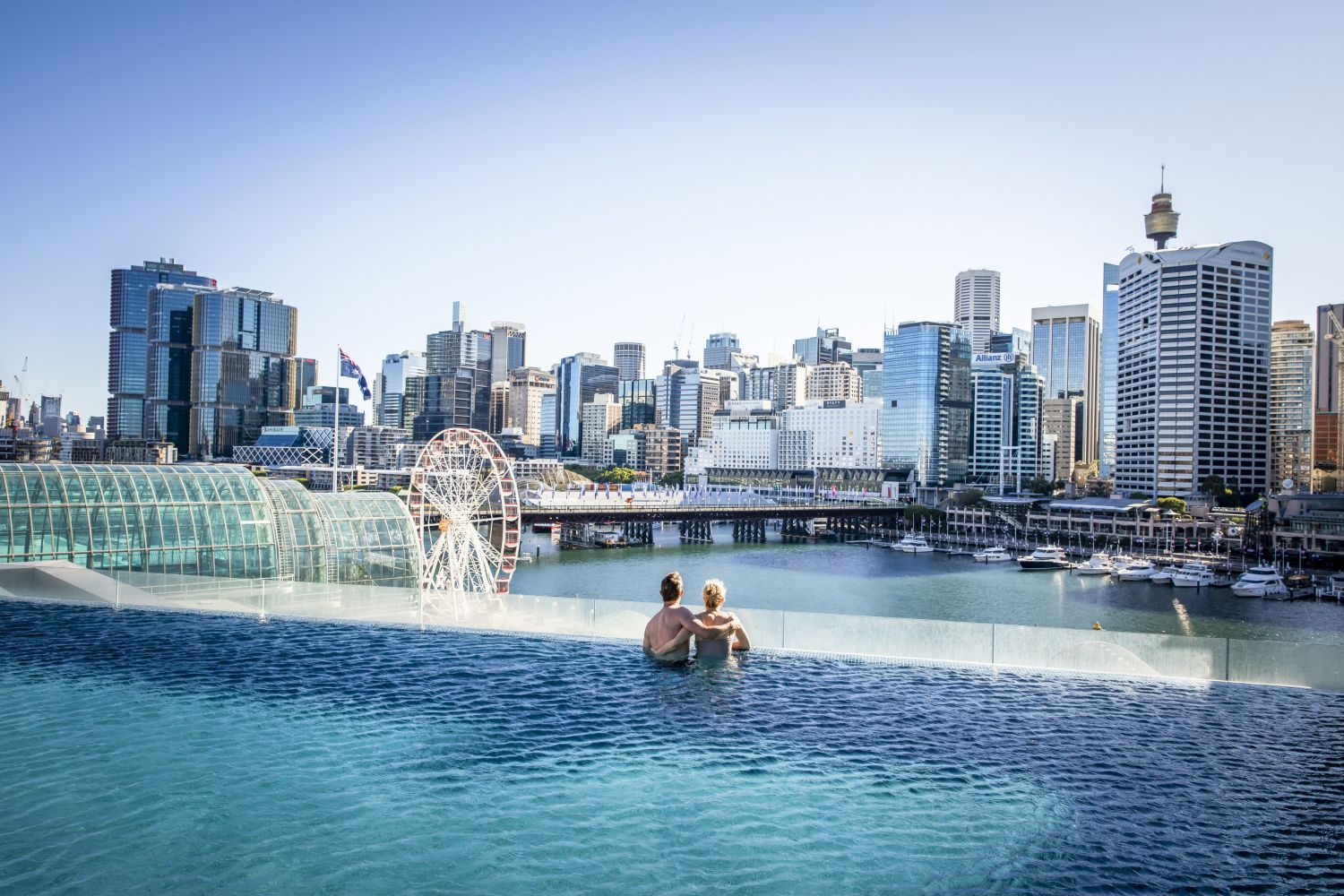 Couple enjoying Sofitel Sydney's rooftop pool with views across Darling Harbour