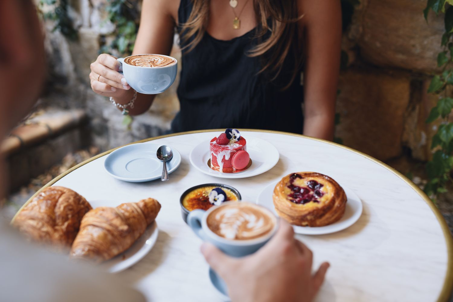 Woman enjoying coffee and pastries at La Renaissance Patisserie and Cafe, The Rocks