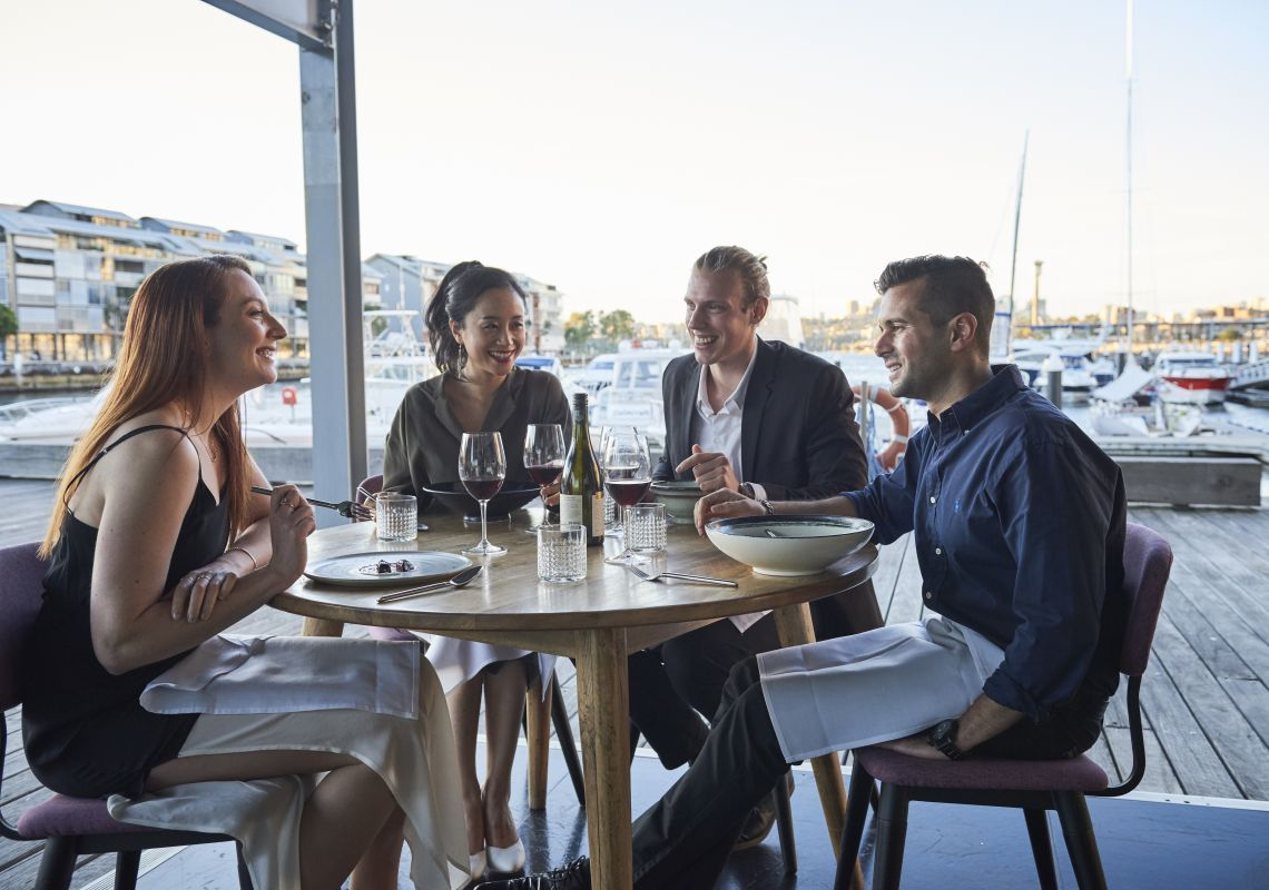 Friends enjoying food and drink at waterside restaurant LuMi Bar & Dining in Pyrmont