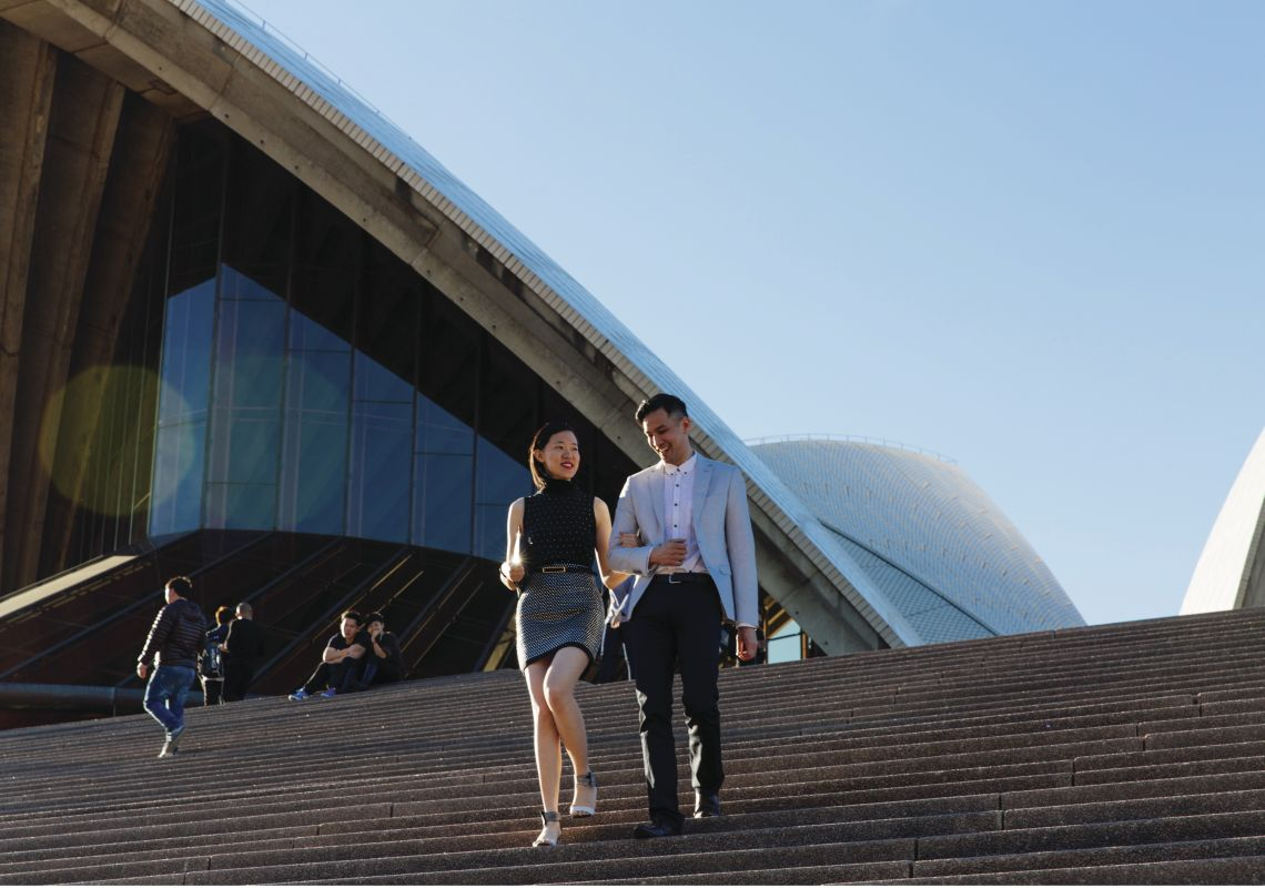 Couple walking down the Sydney Opera House forecourt steps, Bennelong Point