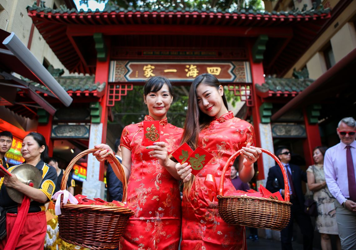 Two women in traditional costume holding red envelopes, Chinatown, Sydney