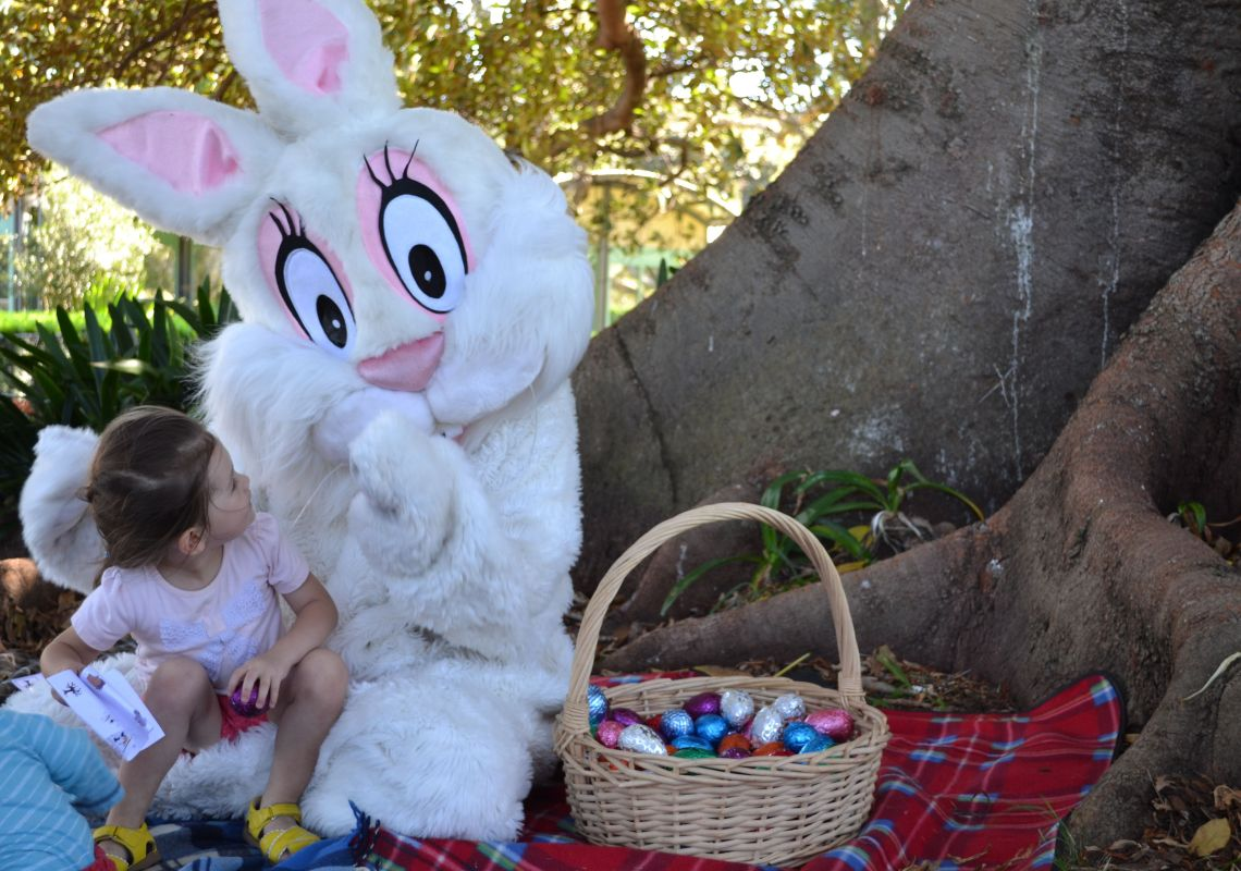 A girl smiling at the Easter bunny in Centennial Park, Sydney