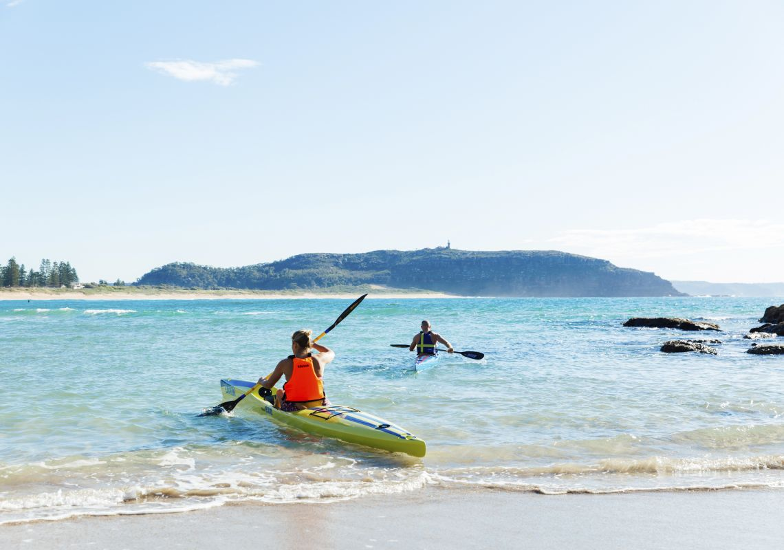 Couple enjoying a morning paddle at Palm Beach on Sydney's northern beaches