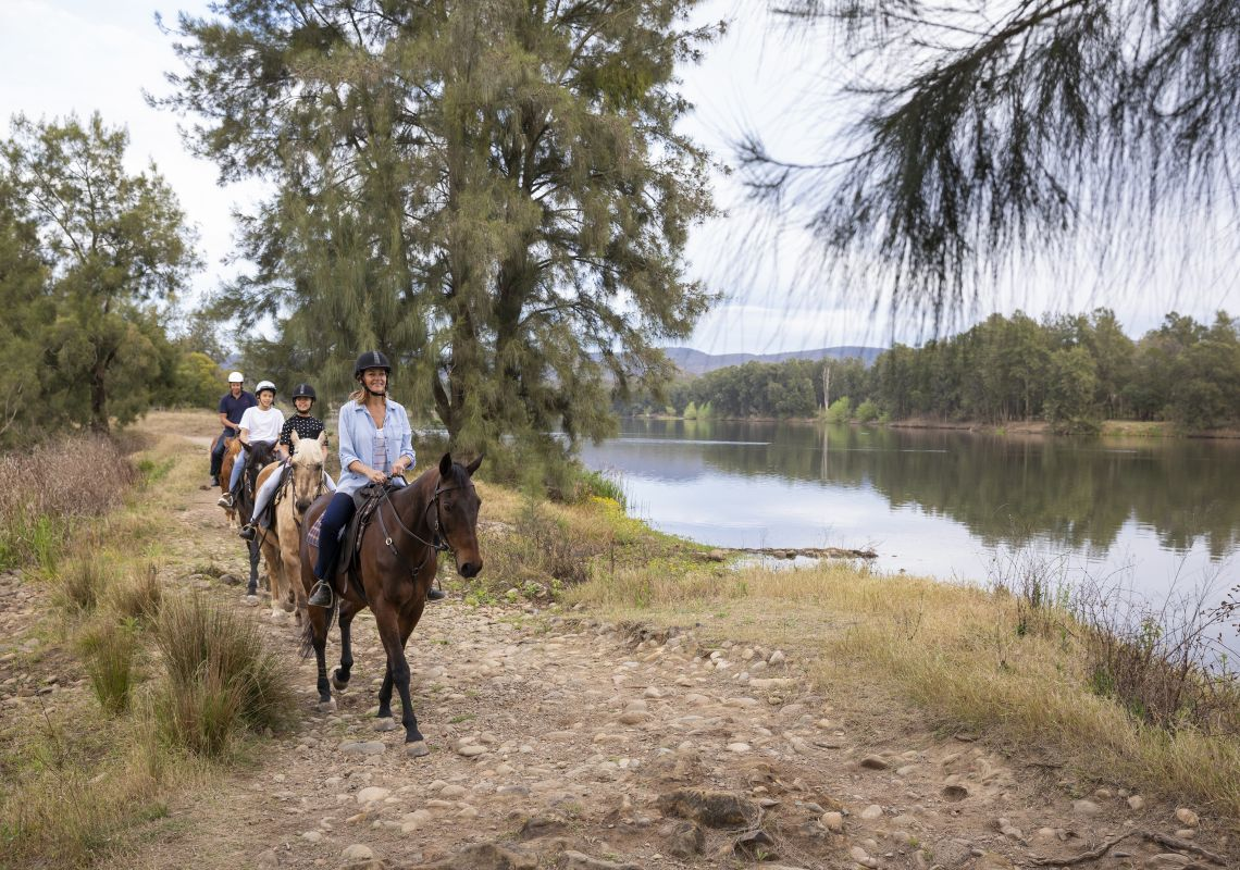 Family enjoying a horseriding experience along the Hawkesbury River with Hawkesbury Valley Equestrian Centre