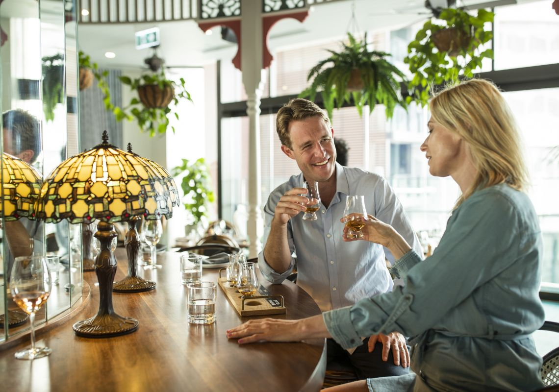 A couple enjoying a whiskey tasting at NOLA Smokehouse and Bar in Barangaroo