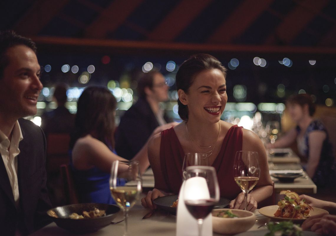 Couple enjoying an evening out with friends at Bennelong Restaurant, Sydney Opera House