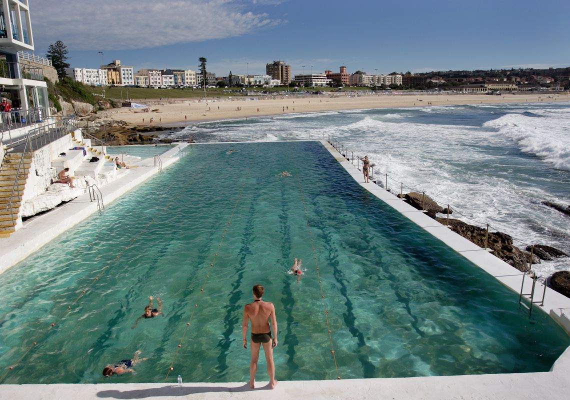 Long shot of swimmers at Bondi Baths, Bondi, with beach in the background, Sydney