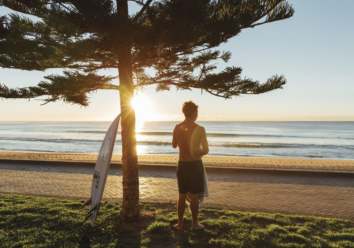 Surfer enjoying the morning sun at Manly Beach in Sydney North