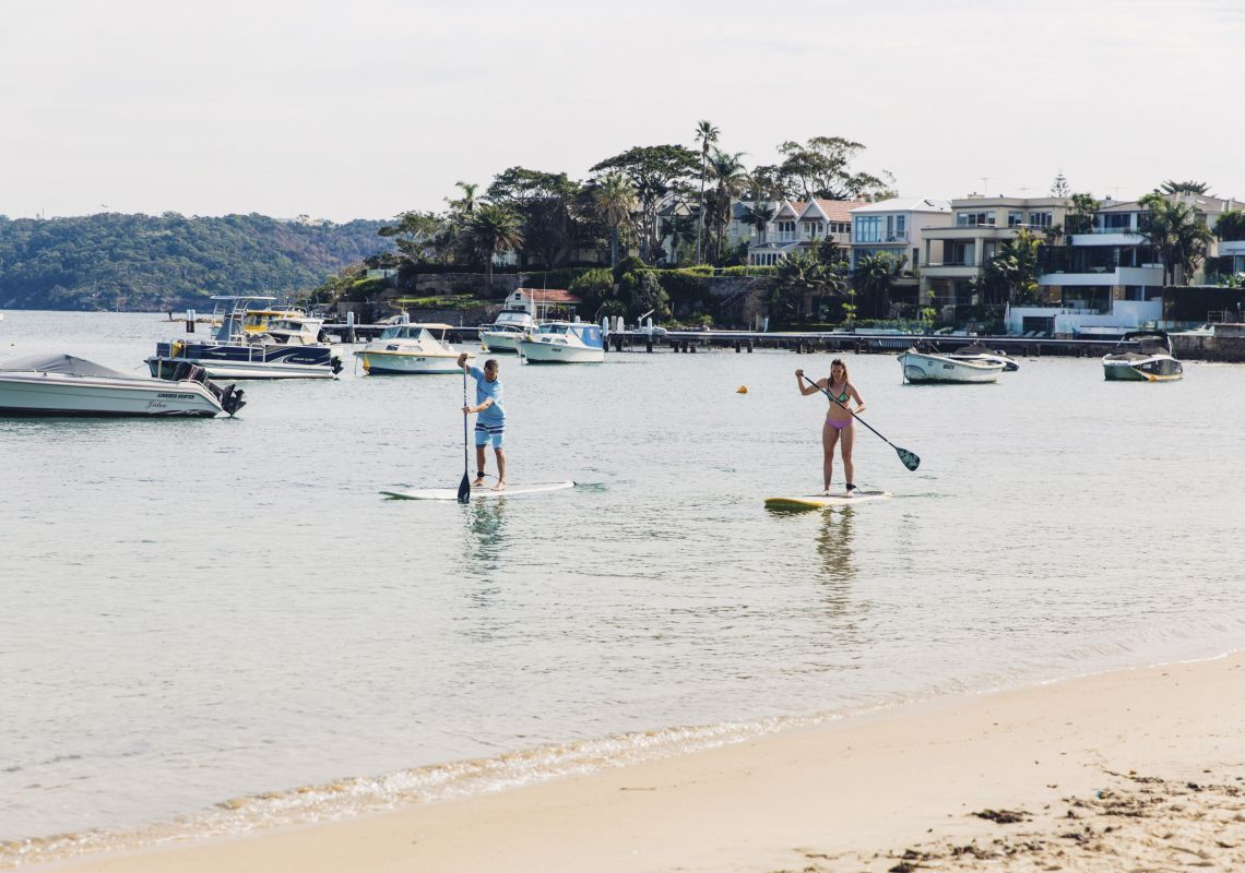 Couple enjoying a morning of stand up paddleboarding at Watsons Bay in Sydney's eastern suburbs