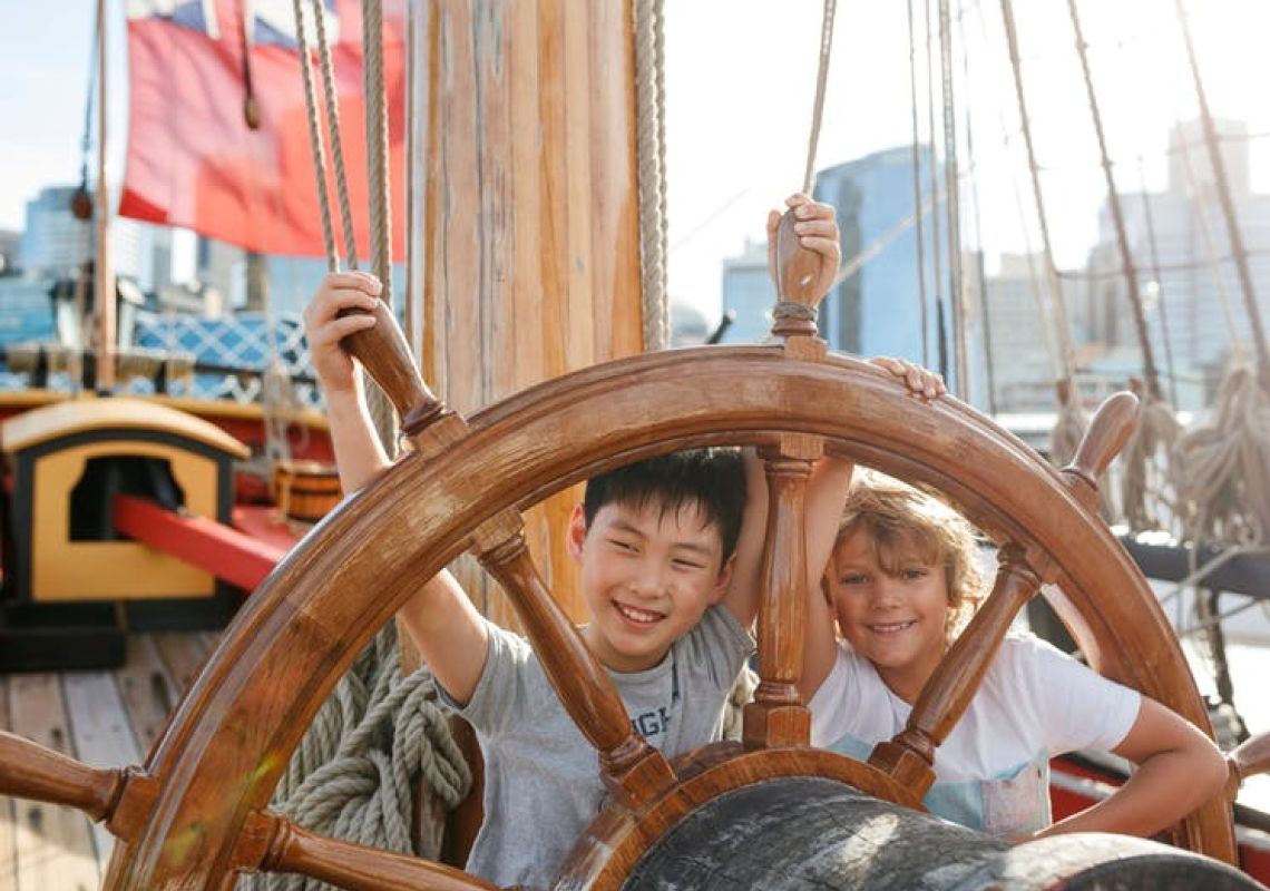 Kids at the wheel of the ship Endeavour in Australian National Maritime Museum, Darling Harbour