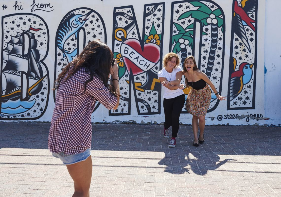 Students taking photos in front of the murals on Bondi Beach in Bondi, Sydney East