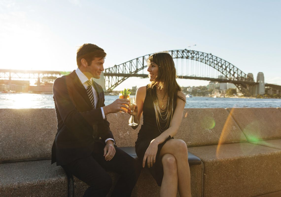 Couple enjoying drinks at sunset by Sydney Harbour, Sydney City