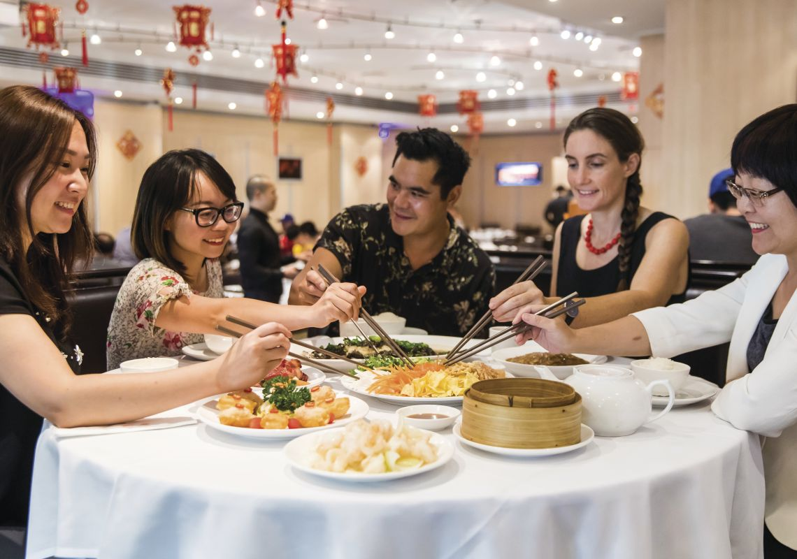 Friends enjoying a prosperity toss at Golden Century Restaurant  during Chinese New Year in Chinatown, Sydney City