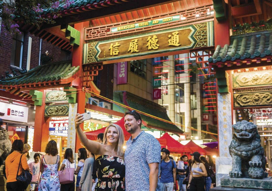 Couple take a selfie in front of the Chinatown gates on Dixon Street, Sydney City