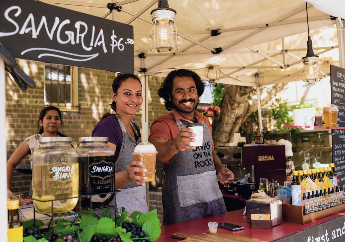 Stall owners with beverages at Friday Foodie Market in The Rocks, Sydney City