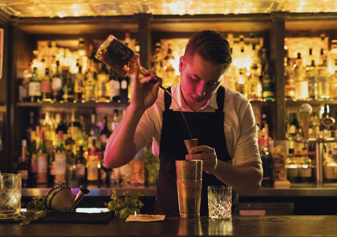 Bartender creating a cocktail at The Doss House bar in The Rocks, Sydney City