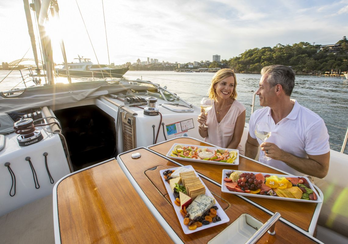 Couple enjoying food and drink on chartered sailing vessel on Sydney Harbour, Sydney City