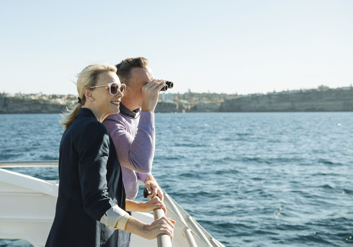 Couple watching out for whales aboard a Captain Cook Cruises cruise vessel off Sydney Heads, Sydney Harbour