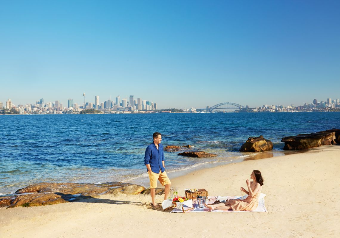 Couple enjoying a picnic with harbour views on Shark Island, Sydney Harbour