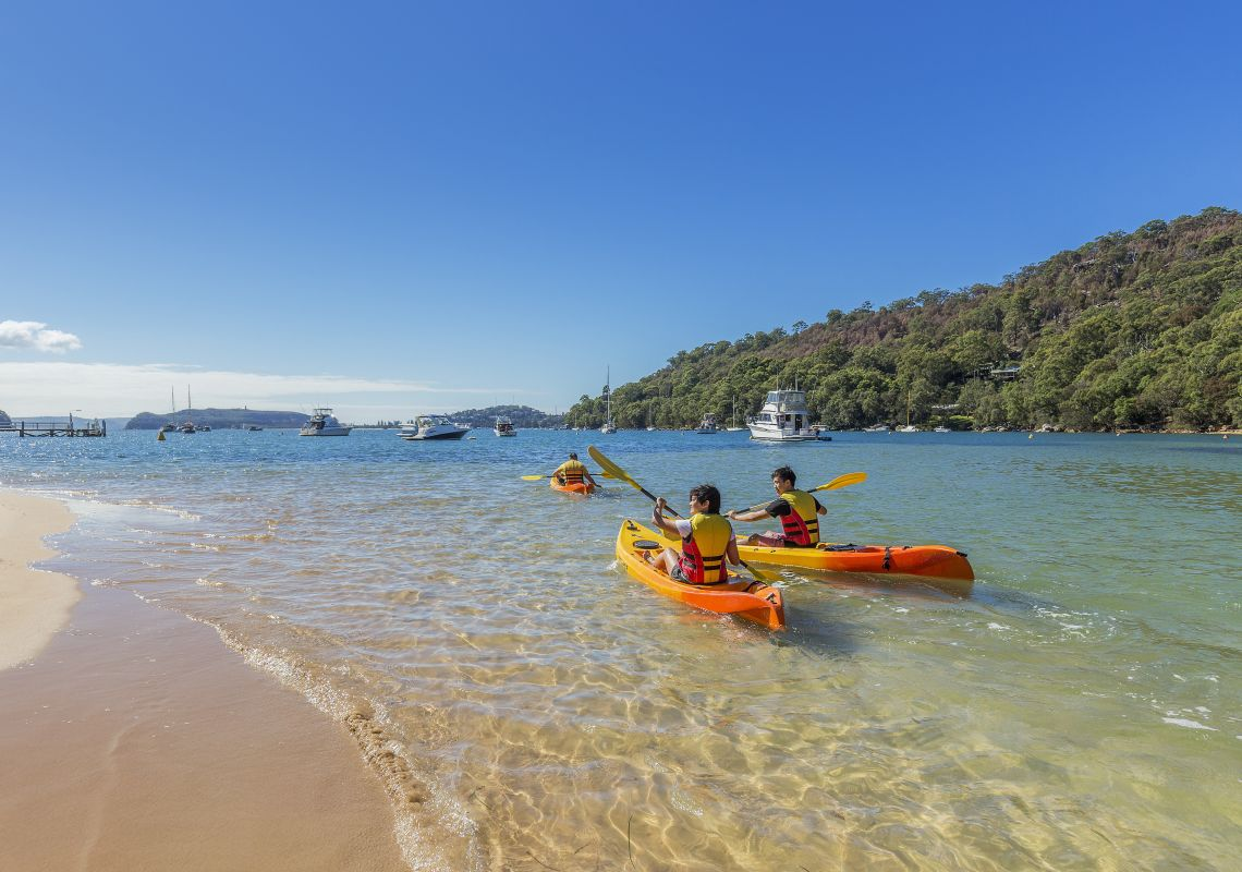 Friends kayaking on Pittwater at The Basin near Coasters Retreat