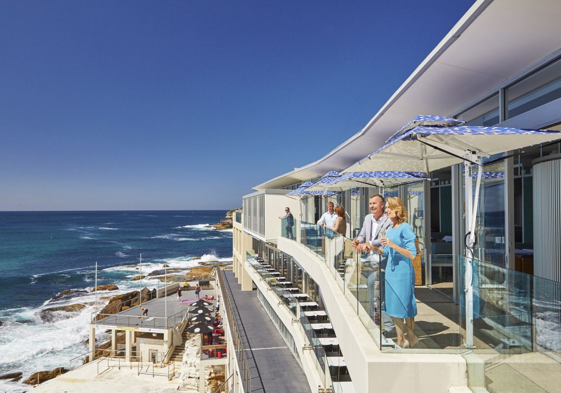 A couple enjoying the views from Icebergs Dining Rooms and Bar, Bondi