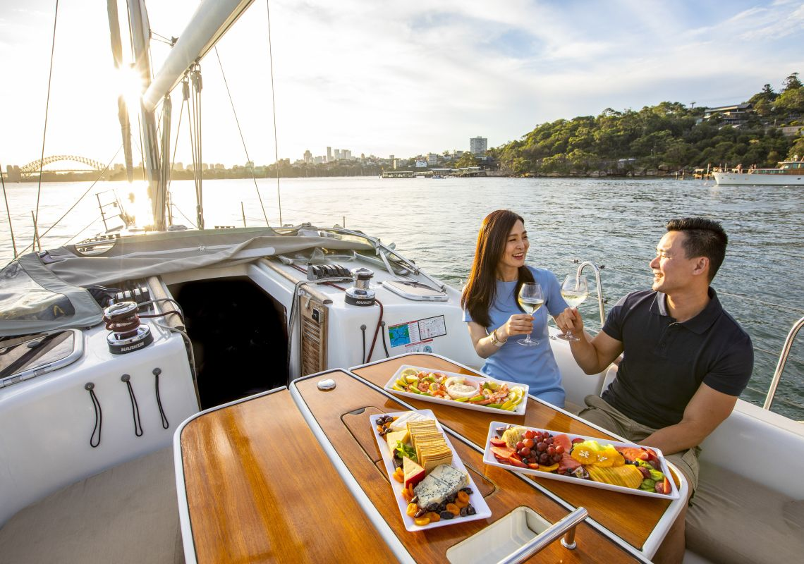 Couple enjoying food and drink on chartered sailing vessel on Sydney Harbour