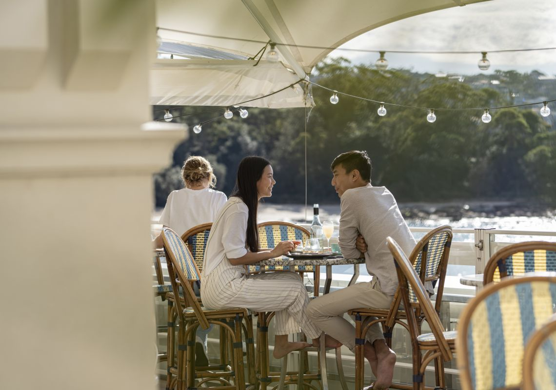 Couple enjoying food and drink with views of Balmoral Beach at Bathers Pavilion, Mosman