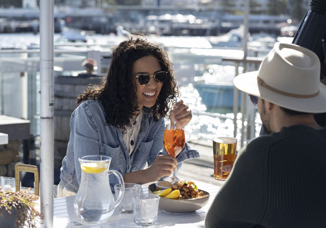 Couple enjoying food and drink at Manly 16ft Skiff Sailing Club, Manly
