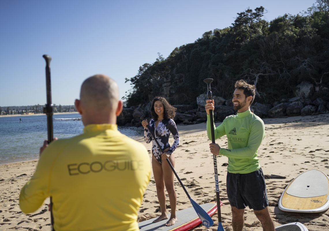 Couple receiving a brief at Shelly Beach for a stand up paddleboarding tour with Ecotreasures, Manly