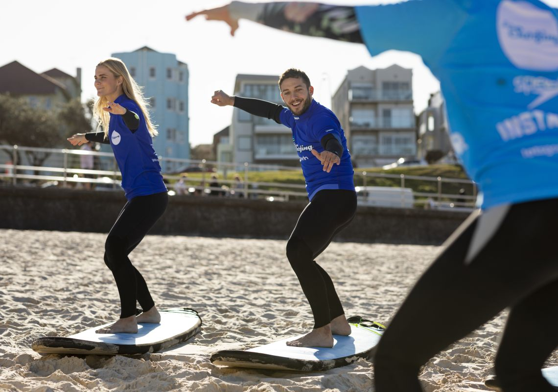 Couple enjoying a surf lesson with Lets Go Surfing, Bondi Beach