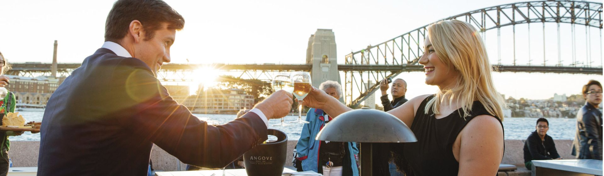 Couple enjoying drinks at sunset by Sydney Harbour