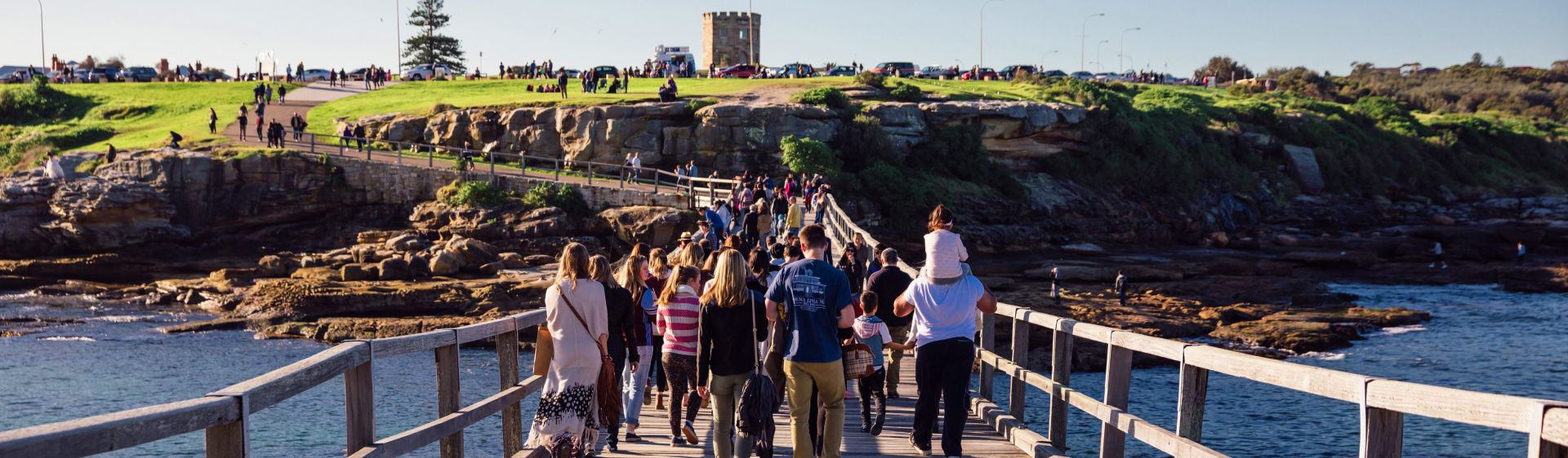 Groups crossing the footbridge at historic Bare Island Fort, La Perouse