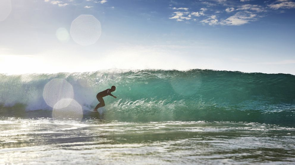 Surfer catches a wave at Mona Vale Beach, North Sydney