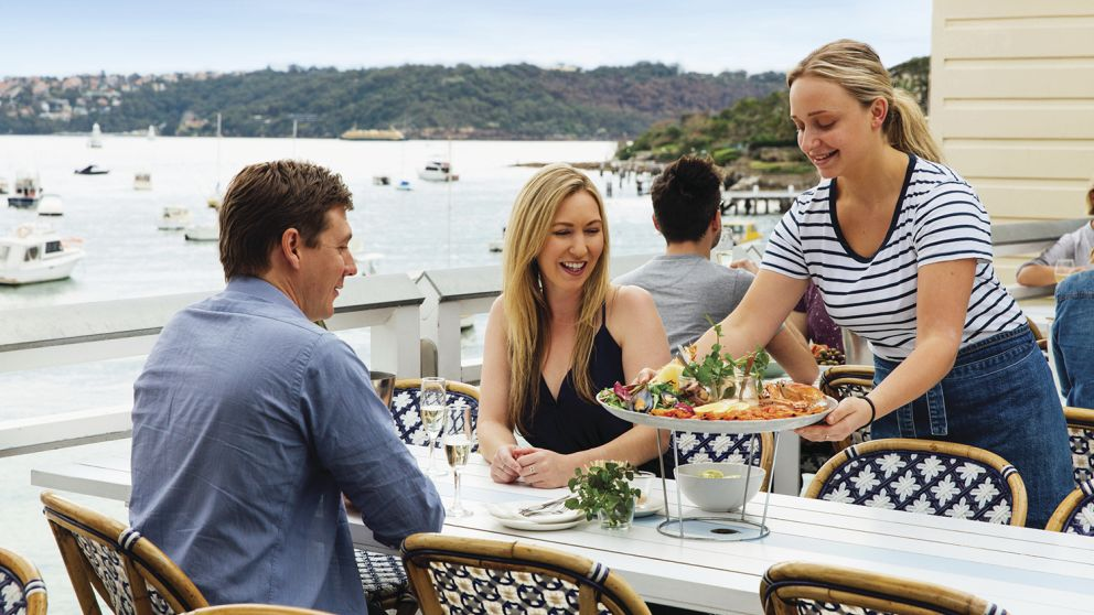 Couple enjoying a seafood platter with waterfront views at Watsons Bay Hotel in Sydney's eastern suburbs