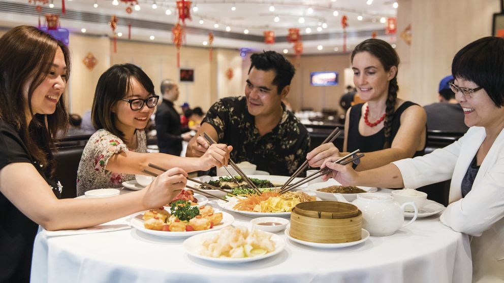 Friends enjoying a prosperity toss at Golden Century Restaurant, Chinatown during Chinese New Year 2018