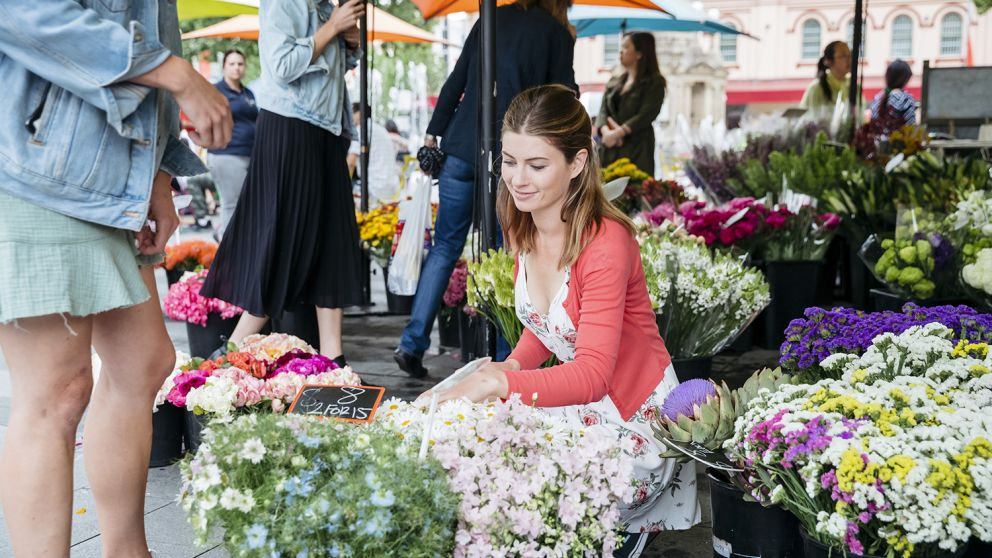 Woman browsing flowers from a florist stall from the Farmers Market in Centenary Square, Parramatta