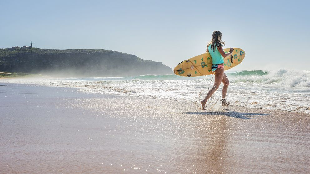 Woman heading out to enjoy a morning surf at Sydney's Palm Beach