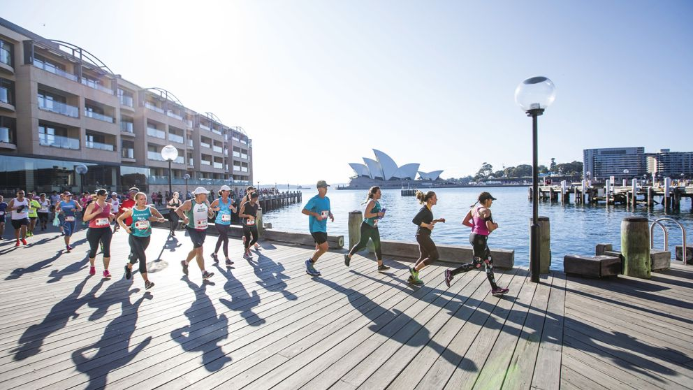 Participants in the Blackmores Sydney Running Festival passing through Campbells Cove with views of the Sydney Opera House