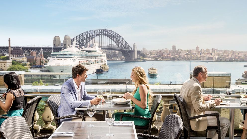 Couple enjoying a lunch with views of a cruise ship at Cafe Sydney on the rooftop of Customs House, Circular Quay