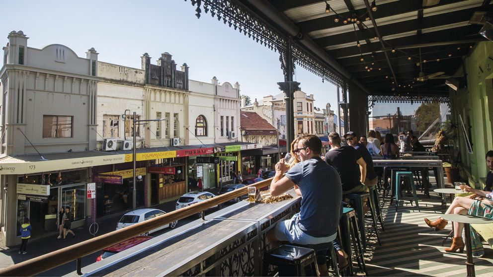 Patrons enjoying a drink on the sun-filled verandah at Newtown Hotel, Newtown
