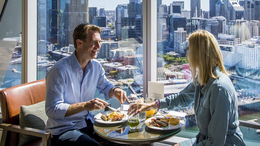 Couple enjoying food and drink at Club Millésime inside Sofitel in Darling Harbour, Sydney City