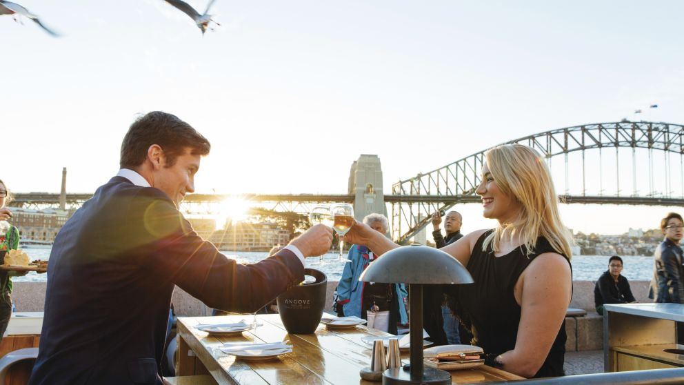 Couple enjoying sunset drinks at the Opera Bar, Sydney Opera House