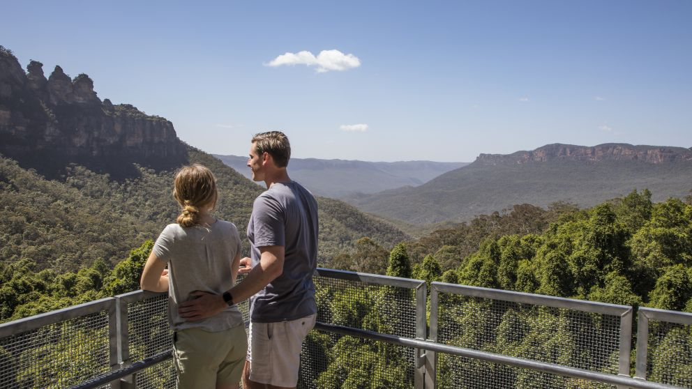 Couple enjoying the views across the Jamison Valley to the Three Sisters from Scenic World, Katoomba