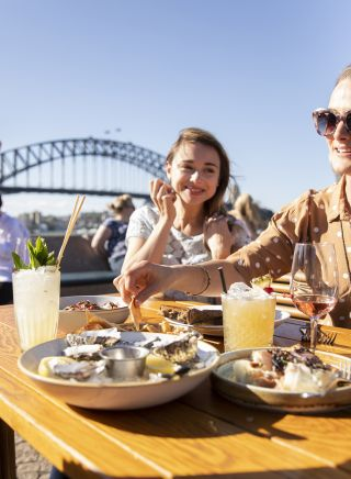 Friends enjoying food and drink at Opera Bar on Sydney Harbour