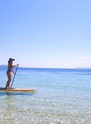 Woman on a paddleboard in Port Stephens with Paddling Eco Adventures